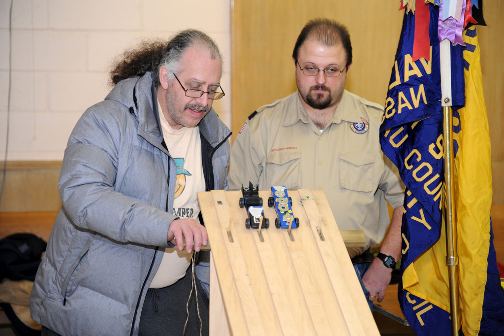 Larry Deckel starts the race while Peter Remsen looks on at Cub Scout Parck 109's Pinewood Derby.