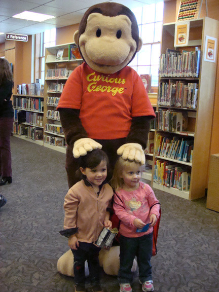 Leah Ploof, left, and Nora Feldman got to meet one of their favorite storybook characters, Curious George, at the grand reopening of the East Rockaway Public Library last Saturday.