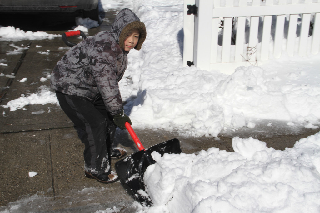 Jimmy You lends his dad a hand by shoveling their walkway.