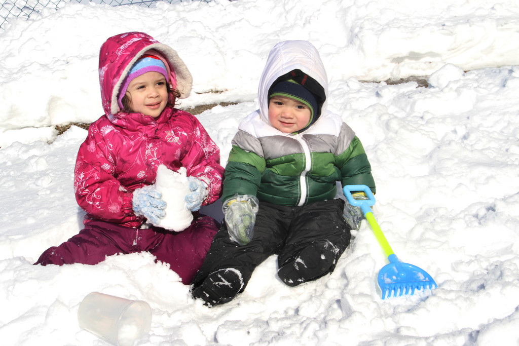 Amy and Jhons Martinez sit in the snow in front of their Elmont home.