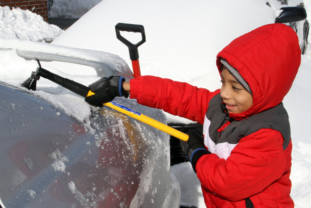 Alex Malaga helps in mom and dad clean their car.