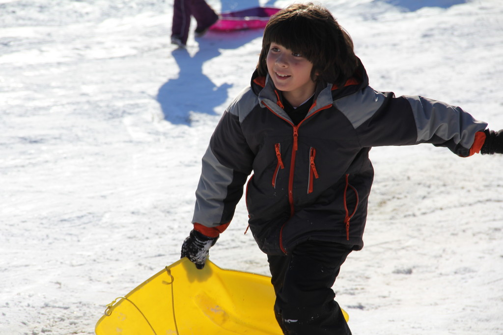 Timmy Warner, 9, runs back up the hill to sled down all over again
