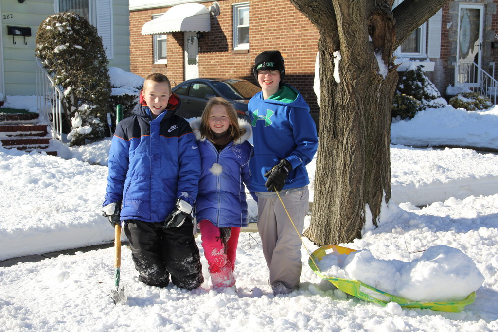 Daniel Mannle, Kristen Greenwood and Matthew Greenwood walk down Claflin Ave. with their sled full of snow boulders in tow
