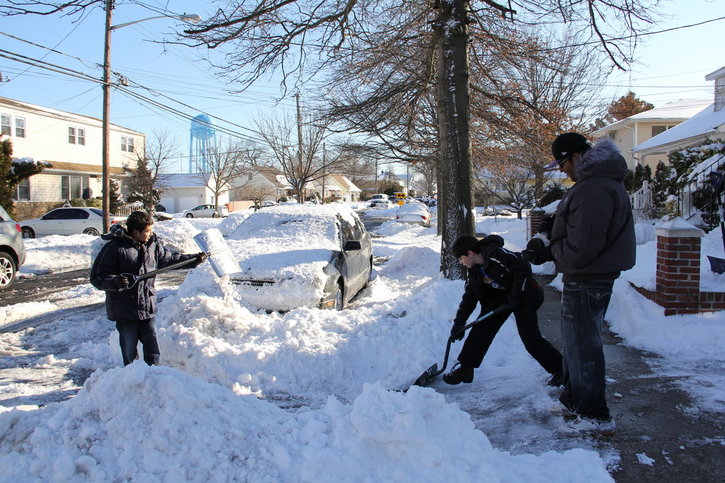 James Fernandez and Free Lamarche shovel out the driveway on Lucille Ave, while friend Akash Nair puts down ice melt
