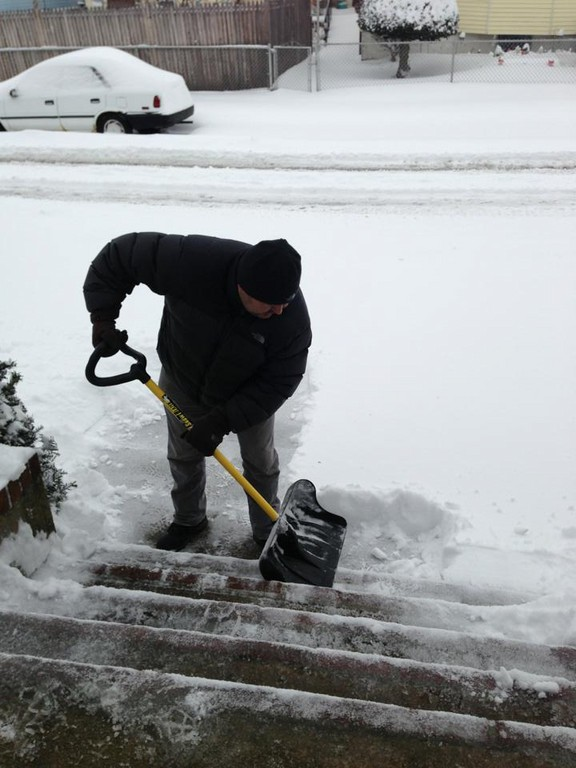 Shoveling snow off the stairs of a house on Maple Road in Inwood.