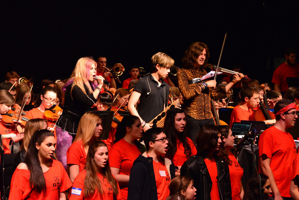 Mark Wood, his wife, Laura, and their son, Elijah, with members of the high school's musical groups.
