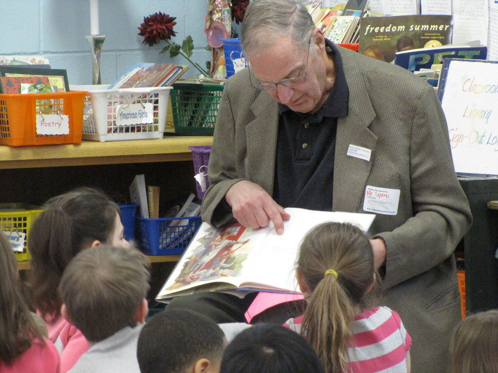 Former Board of Education President Allenby Lyson shares a book with children at School #5.