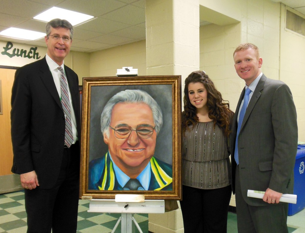 Jen Varvaro, a senior at Lynbrook High School, showed off her portrait of the much-beloved Dr. Santo Barbarino at the Feb. 6 Board of Education meeting. She was joined by Principal Joe Rainis, left, and Assistant Principal Matt Sarosy.