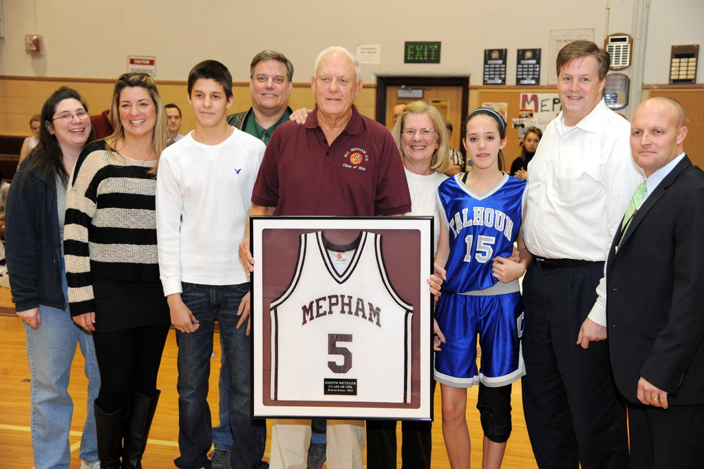 Mepham basketball great Joseph Metzger III recently had his number retired during a surprise ceremony at his alma mater. Joining him to celebrate were, from left, daughter-in-law Mary Ann Metzger, daughter Tammy McLoughlin, grandson Austin McLoughlin, son David Metzger, his wife, Joyce, granddaughter Bailey McLoughlin, son-in-law Brian McLoughlin and Mepham Principal Michael Harrington.