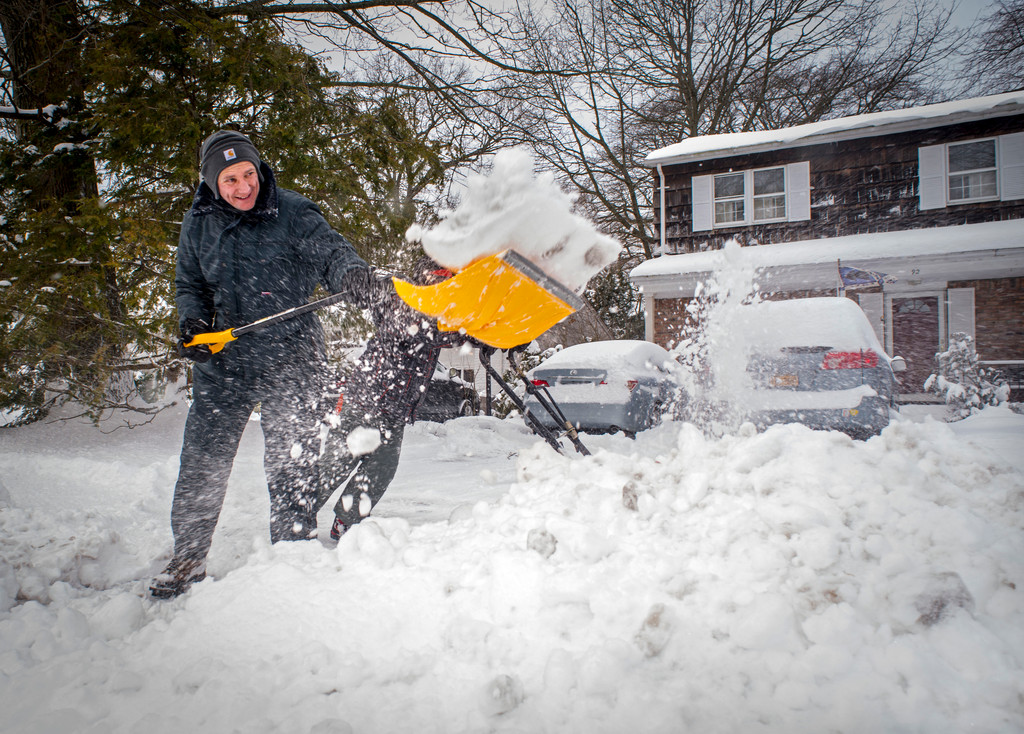 Adrian Goodlad worked to clear the snow from the front walkway of his home on Riverside Drive.