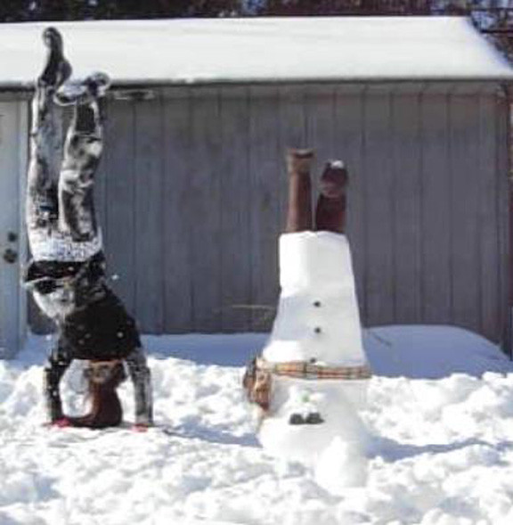 Christina Mendoza, a sophomore at Clarke High School, with her upside-down snowman in her backyard on Avis Drive.