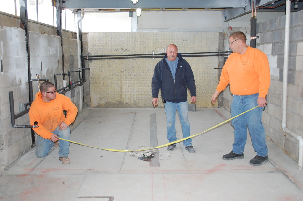 Village workers, from left, Nick Vassilou, Glenn Kohlenberg and Danny Vecchione, take measurements in one of the pool locker rooms currently under renovation.