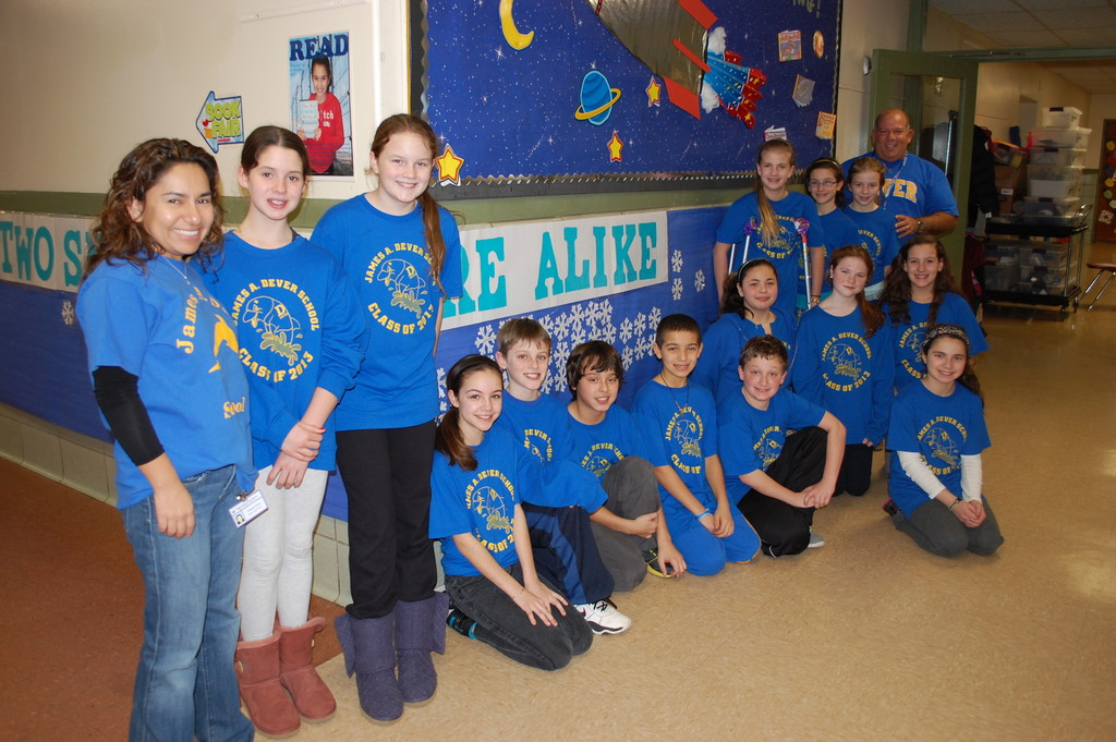 "Students at the James A. Dever School in District 13, joined by social worker Yashmira Devine, left, and Principal Darren Gruen, right, contributed to a banner, ""No two snowflakes are alike."" Each child wrote their name on a paper snowflake, and one unique trait about themselves."