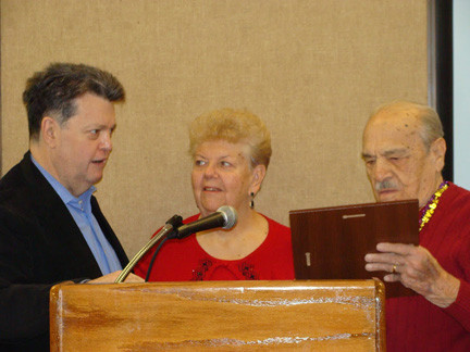 Mayor Bill Hendrick congratulated Paul Sci and presented him with a citation from the Village of Lynbrook as his wife, Katherine, looked on.