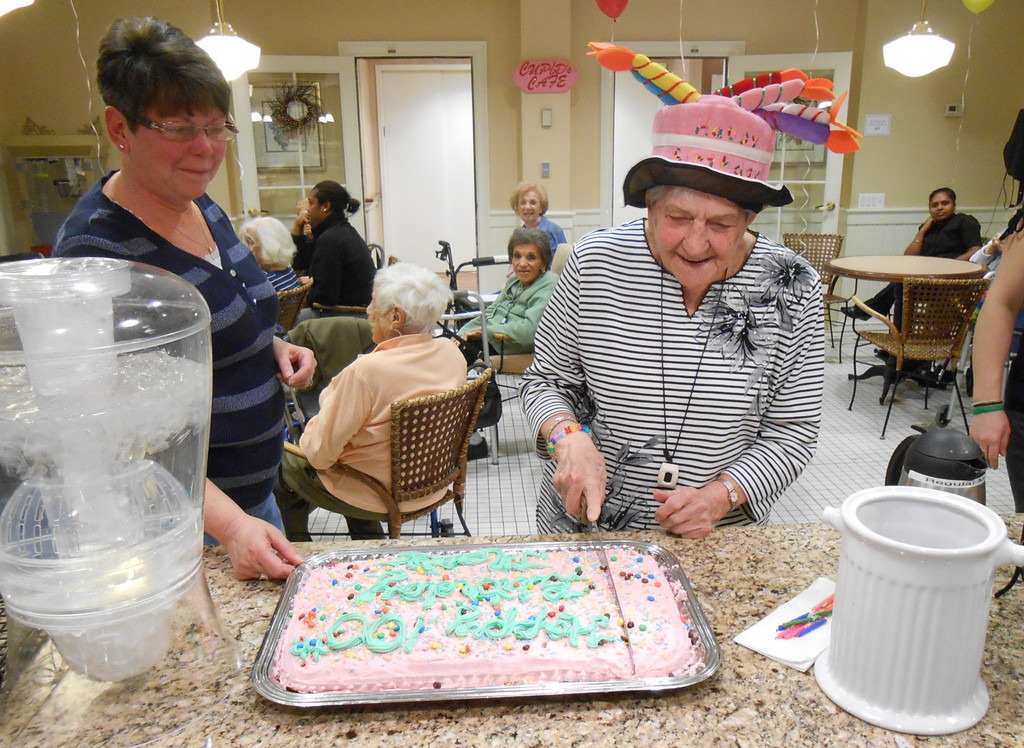 Marie Lockwood cut a slice of the beautiful birthday cake.