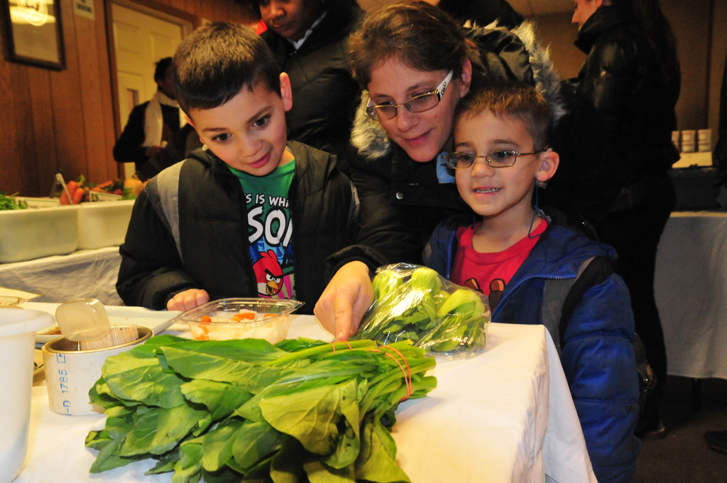 Brendan and Hunter Artzt, 6 and 8, and their mom, Debbie, eyed some spinach at the first Baldwin winter farmers market.