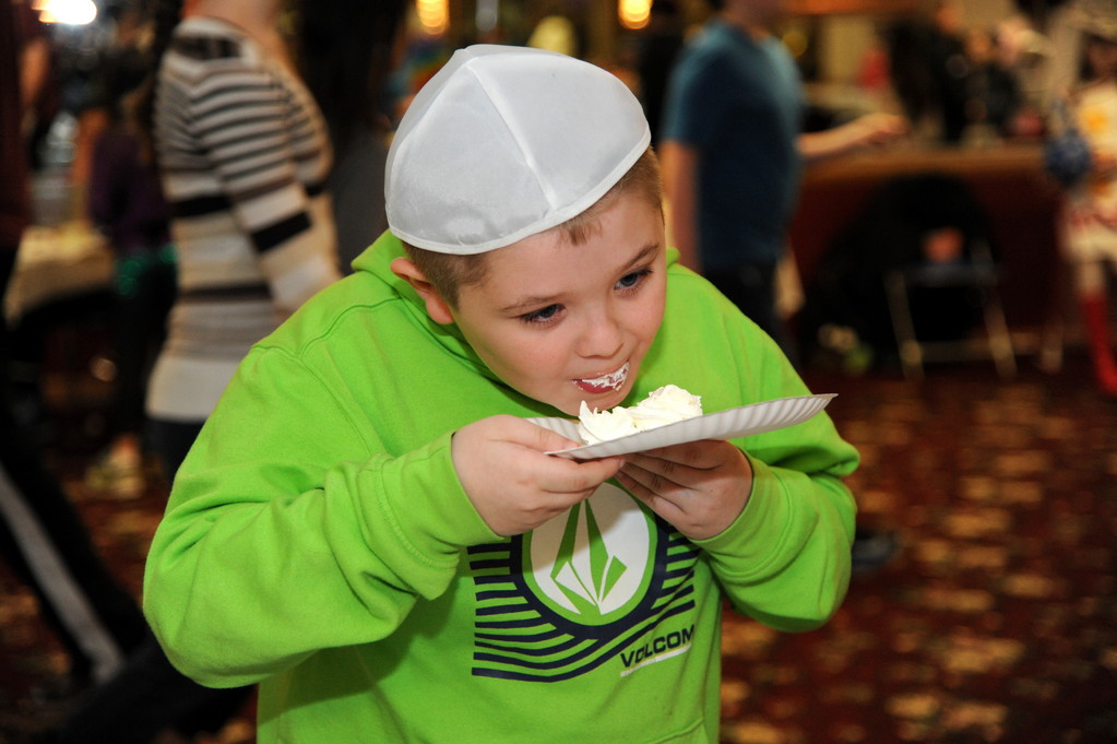 Temple Hillel's Purim carnival included many treats for the children. Left, Jordan Mackiney, 8, licked the whip cream to get to the Tootisie Roll.