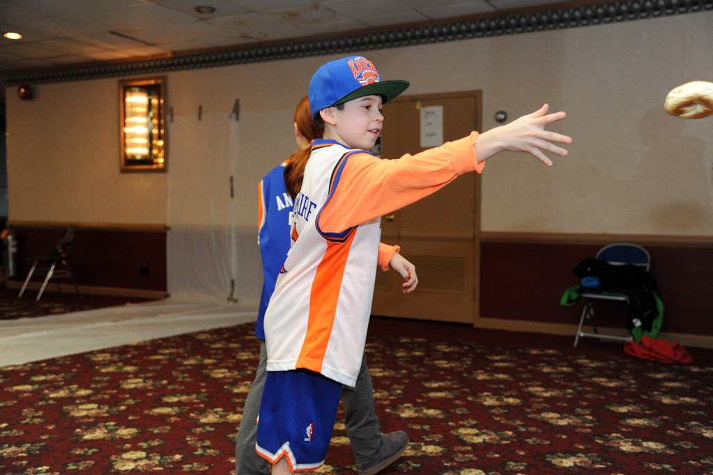 Games and activities were part of the temple's Purim carnival. Above, Ian Panzarella, 9, took part in the bagel toss.