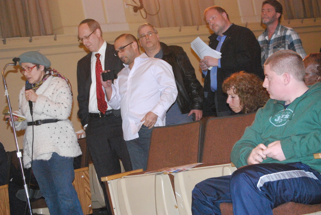 Dror Zar holding microphone, Nidia Mondejar and other residents waited for a response from representatives of Simone Development and Mt. Sinai at a town hall meeting on Feb. 27.