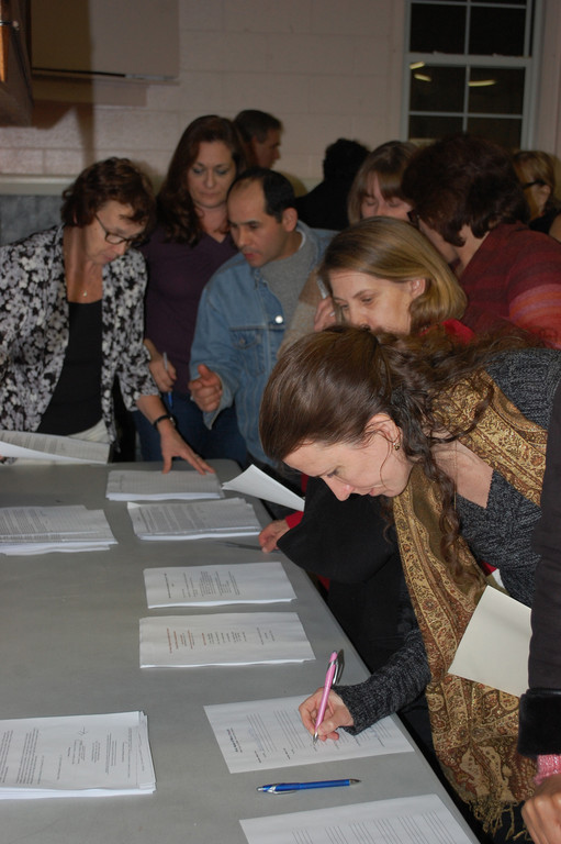 Private-School parents signed petitions at Holy Name of Mary School on Feb. 27 in opposition to the high school's transportation plan.