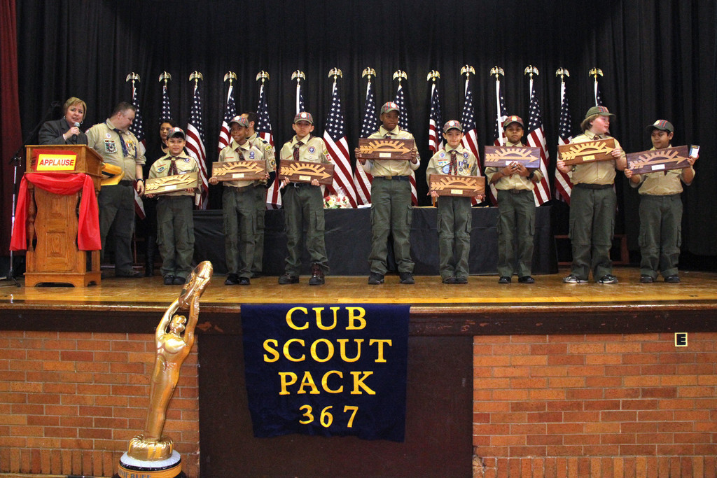 Supervisor Kate Murray, left, presented scouts, from left, Peter Castellanos, Christopher Coley, Joseph Correa, Akin Olowofela, Matthew Pifiero, Jayden Times, James Wheeler and Brandon Yu with their Arrow of Light Awards on March 2 at Holy Name of Mary School.