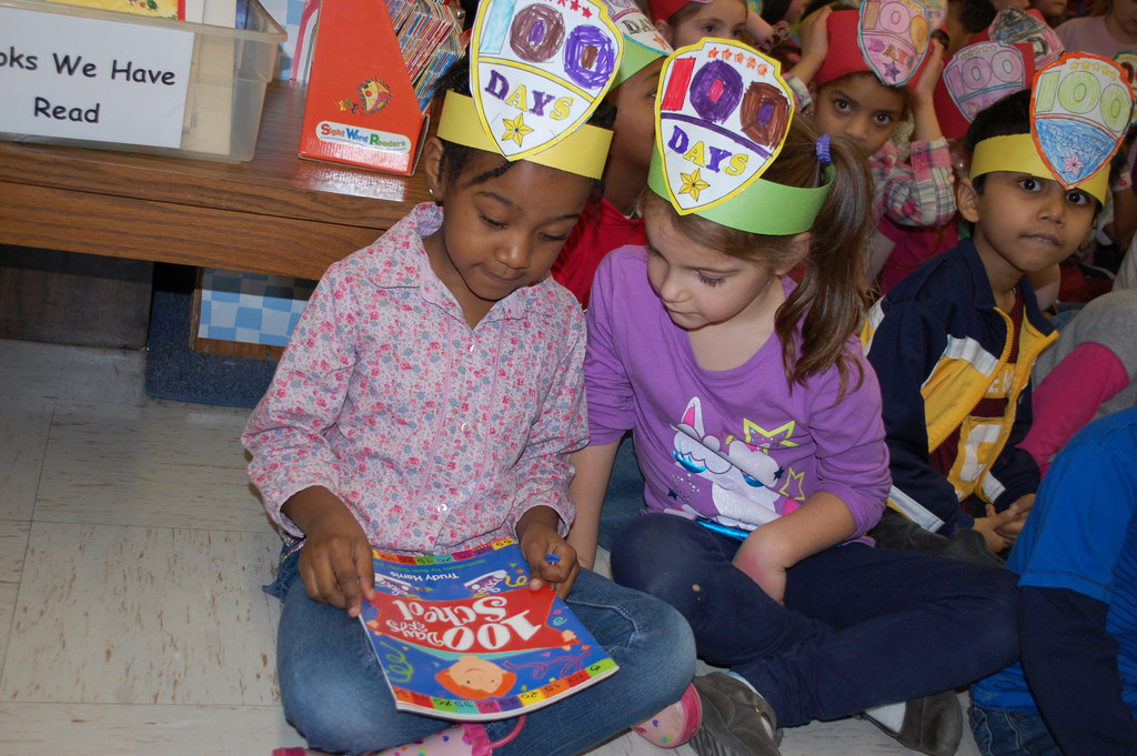 Dever students Celine Buly and Rachel Casalo read a book about the 100th day of school.