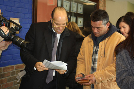 Cantor Fitzgerald Chairman and CEO Howard Lutnick, left, helped one resident find his way at the distribution center set up at Long Beach Middle School.