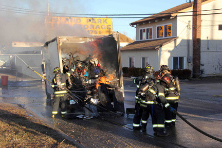Volunteer firefighters from Island Park fight the truck fire.