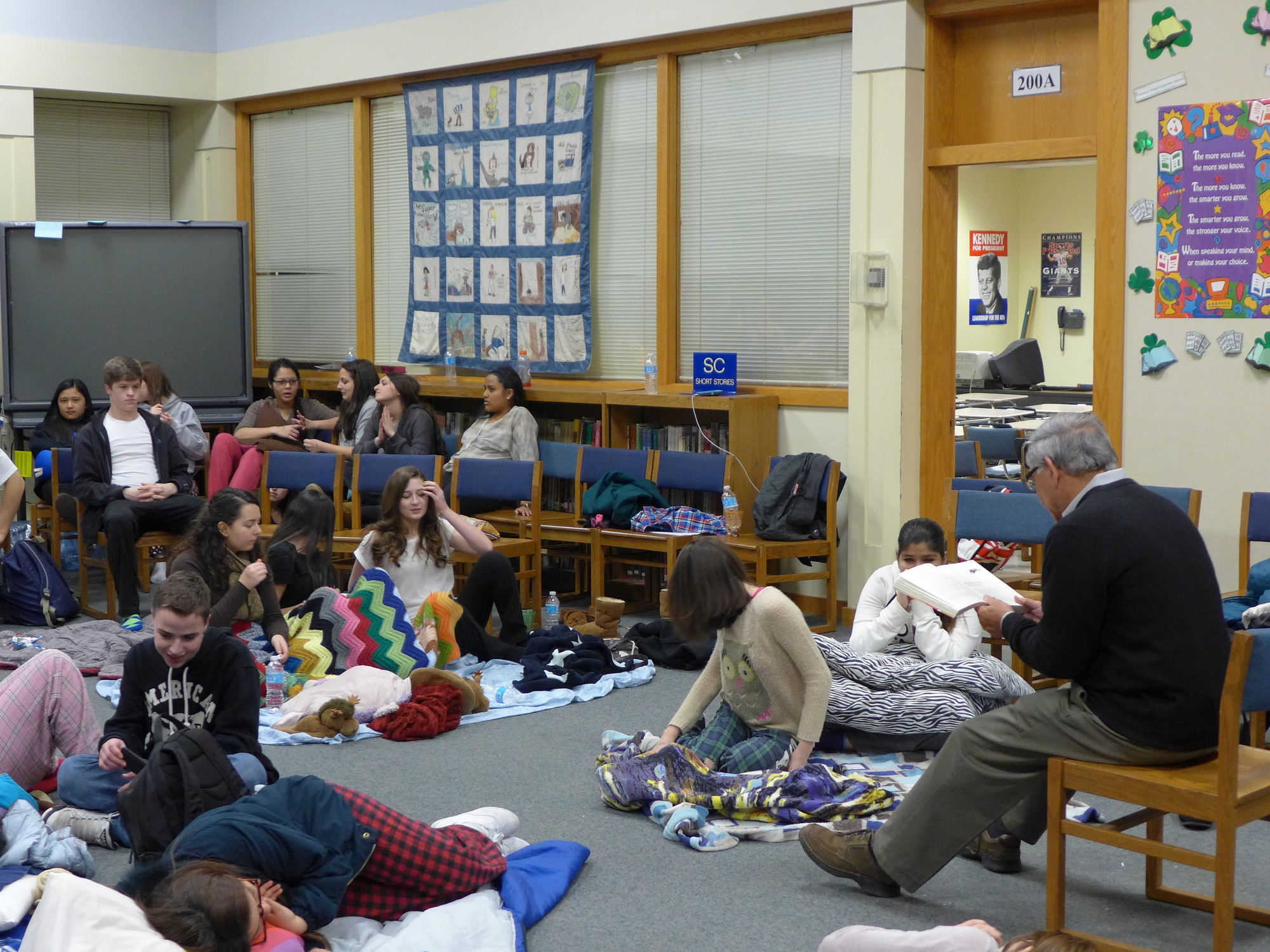 Superintendent of schools Dr. Herb Brown  gets comfortable reading The Odyssey to seniors at Oceanside High School during an all-night reading of the book.