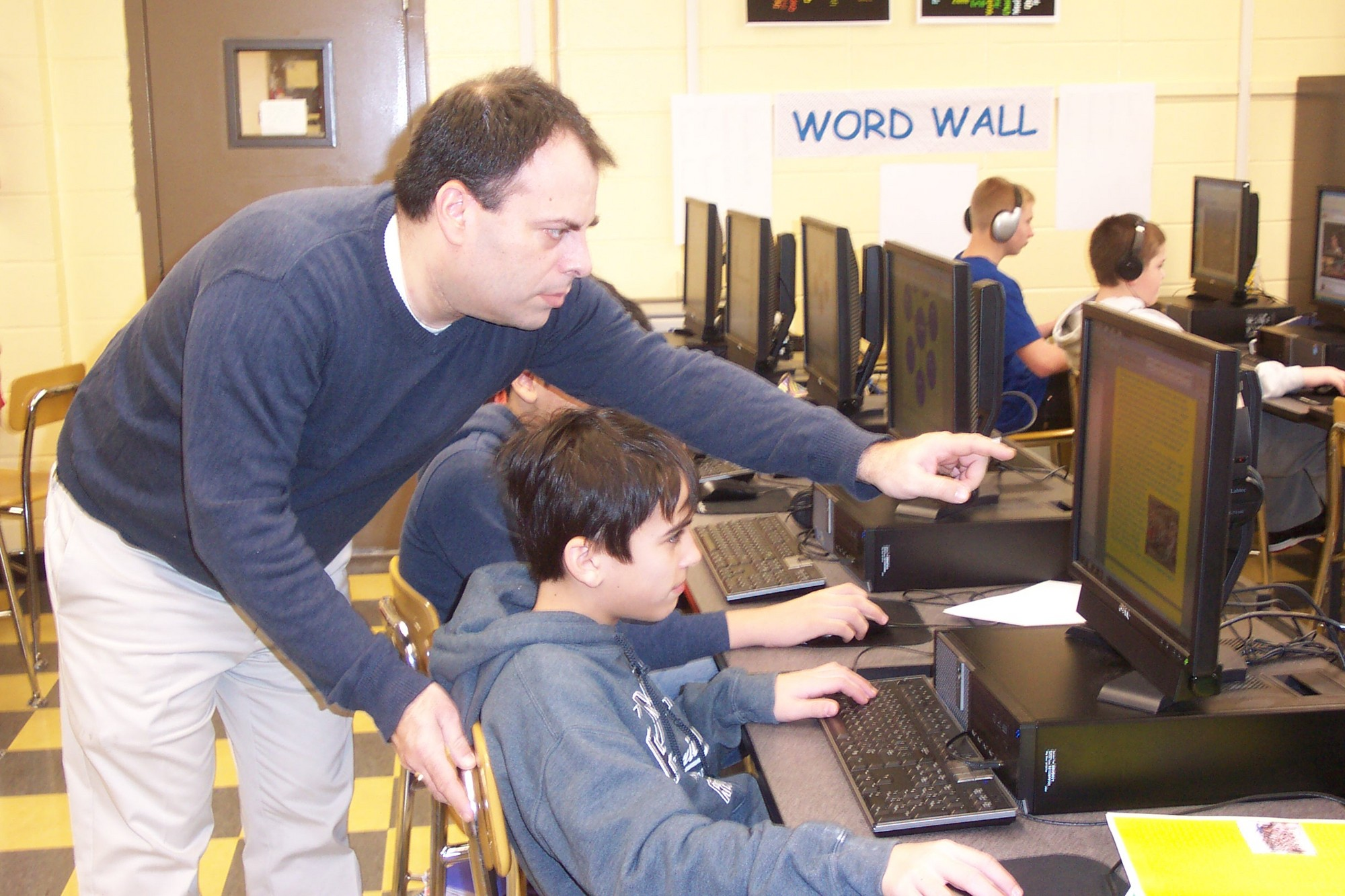Teacher Gabriel D'Auria is shown here helping Raffaele Pupa design a layout of one of his pages.