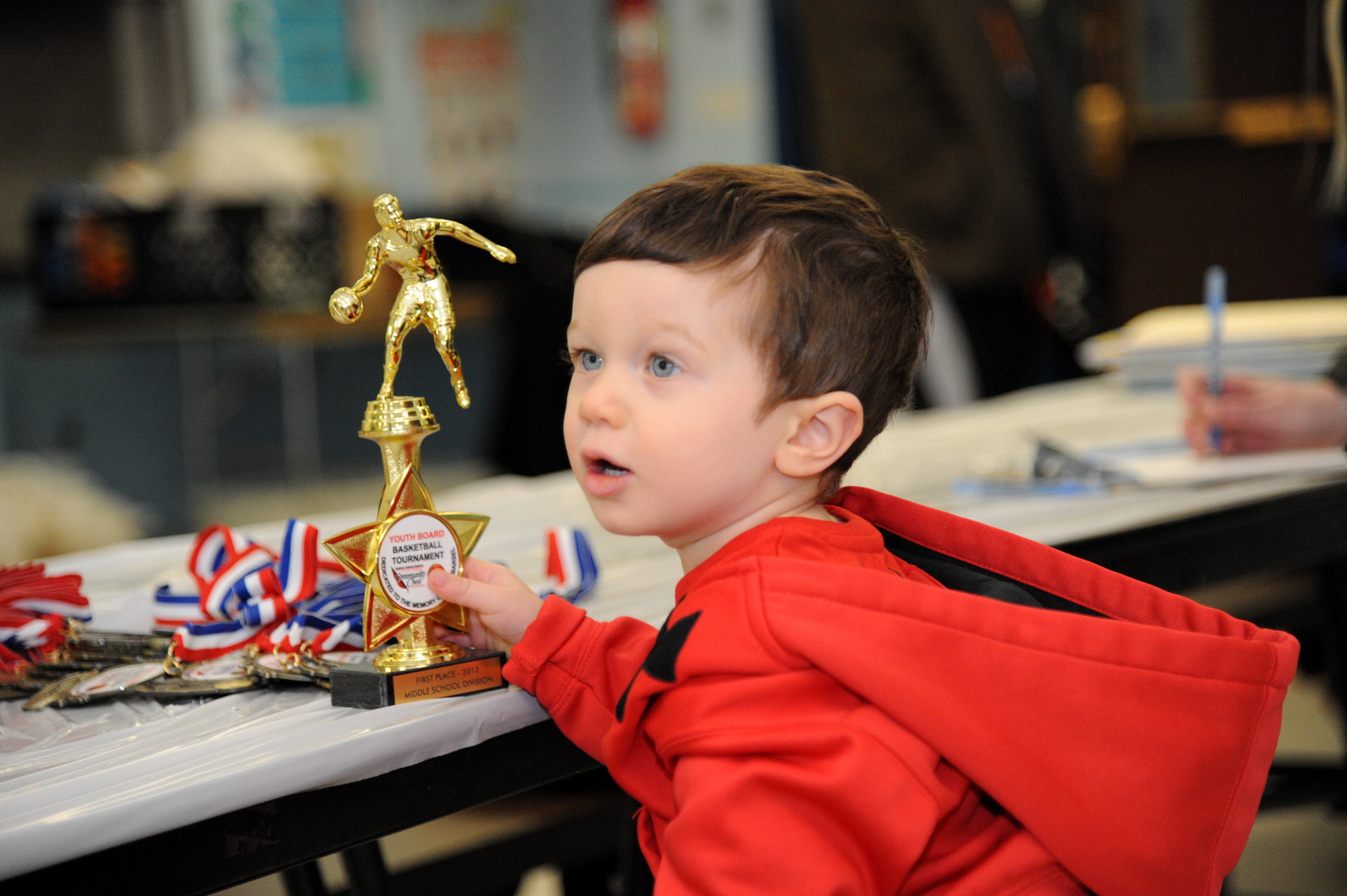 Eyes on the prize: Nearly 2-year-old Addison Dugan, a relative of Adam Barsel, views one of the trophies presented to the winning teamas.