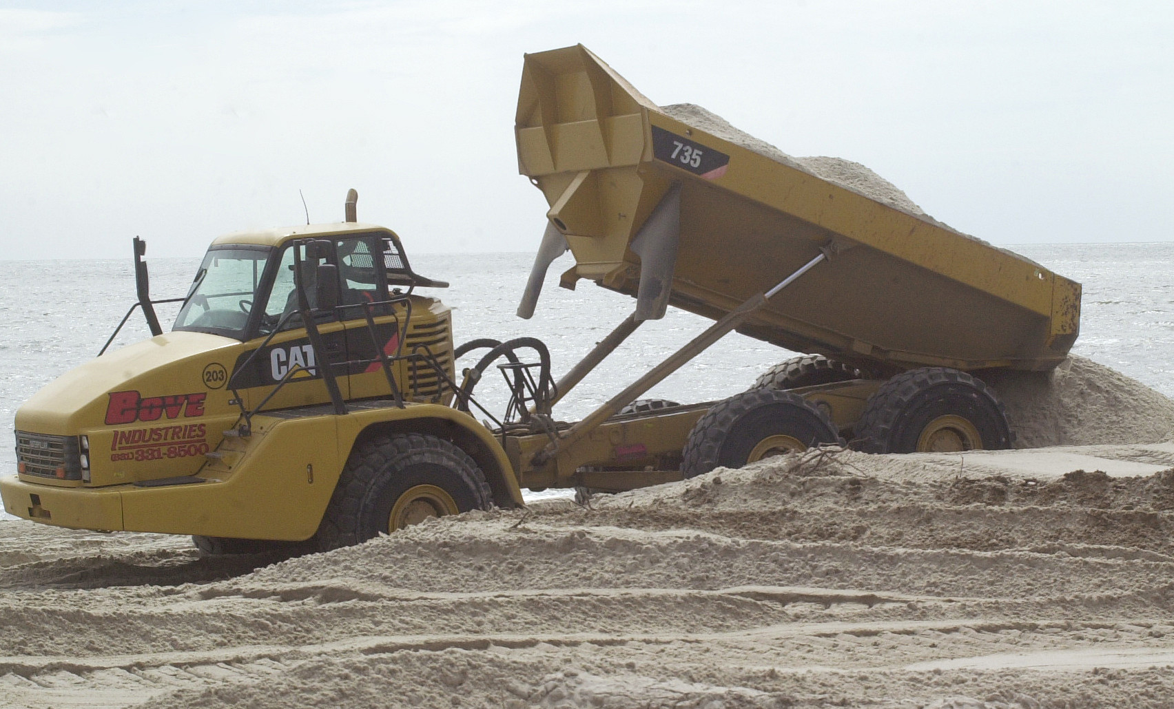 The state is using massive dump trucks to unload 800,000 cubic yards of sand to build dunes along the Ocean Parkway.