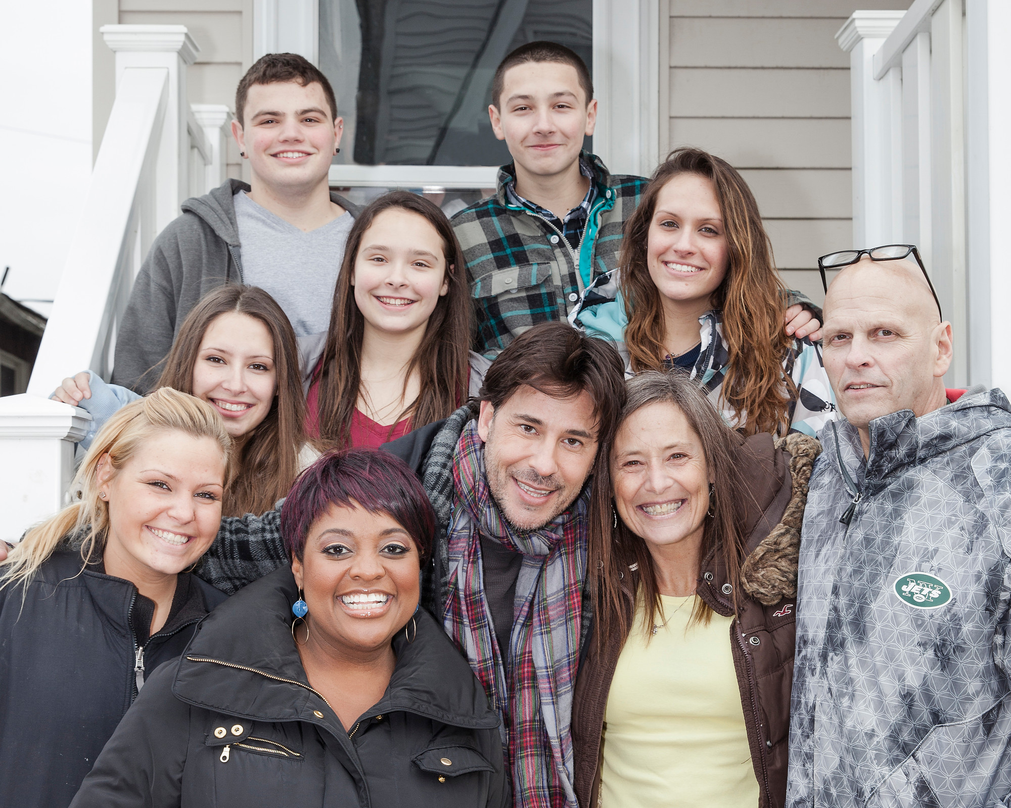 "TV host Ricky Paull Goldin, center, and ""The View's"" Sherri Shepherd, bottom left, with the Enright family, after they broke the news that their home is slated for   a makeover on ""Spontaneous Construction."""