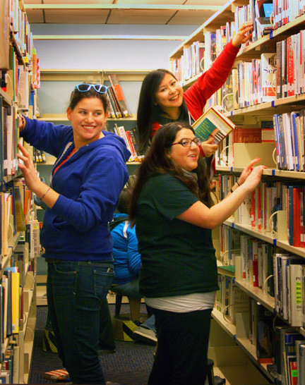 Volunteers Starr Lederer, left, Denise Ferias and Bari Jay unpacked and organized books on the first floor of the library on March 9.