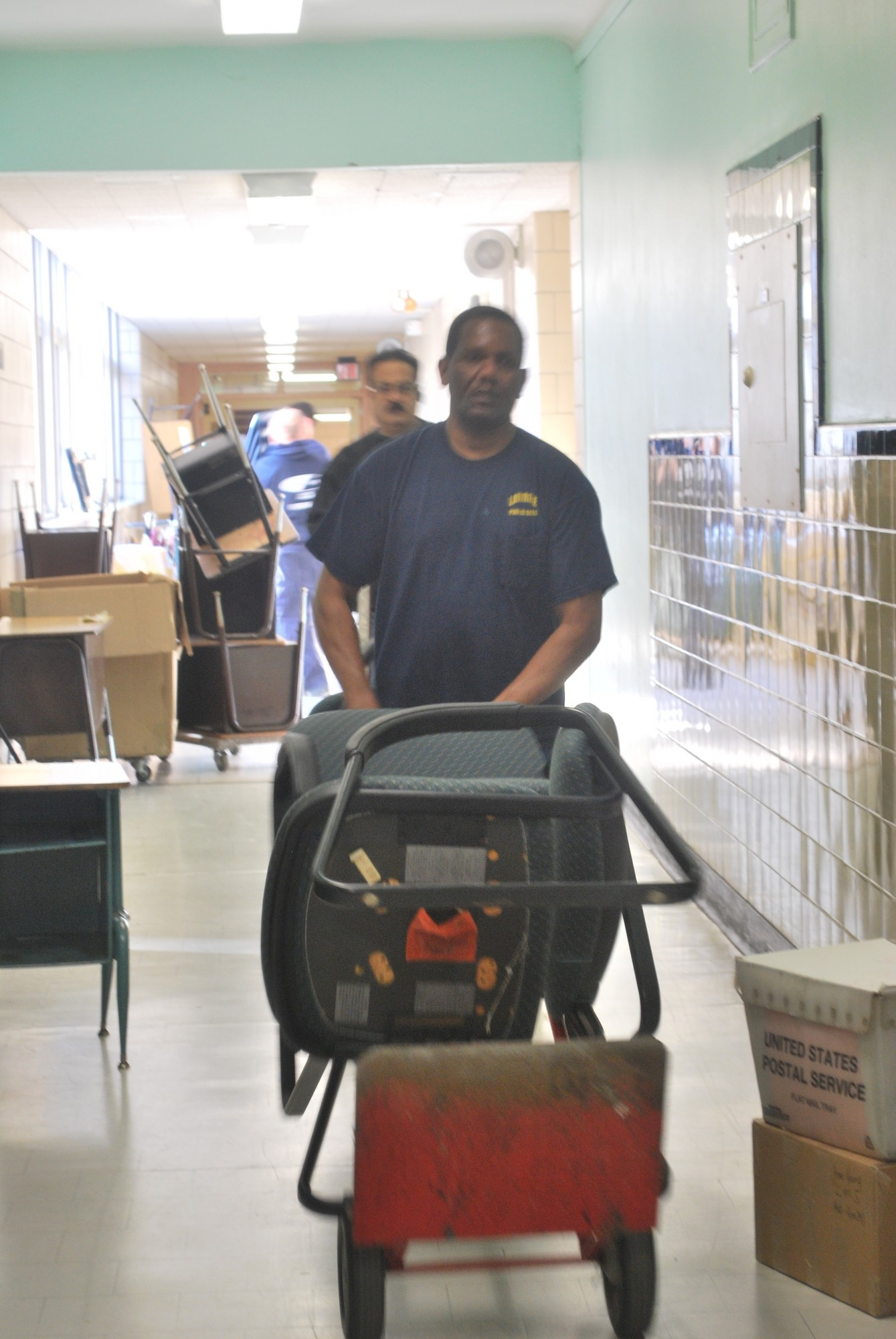 The Lawrence School District was expected to return to normal operations on Wednesday, when the high school was to reopen. District worker Prince Singh moved chairs at the middle school last week.