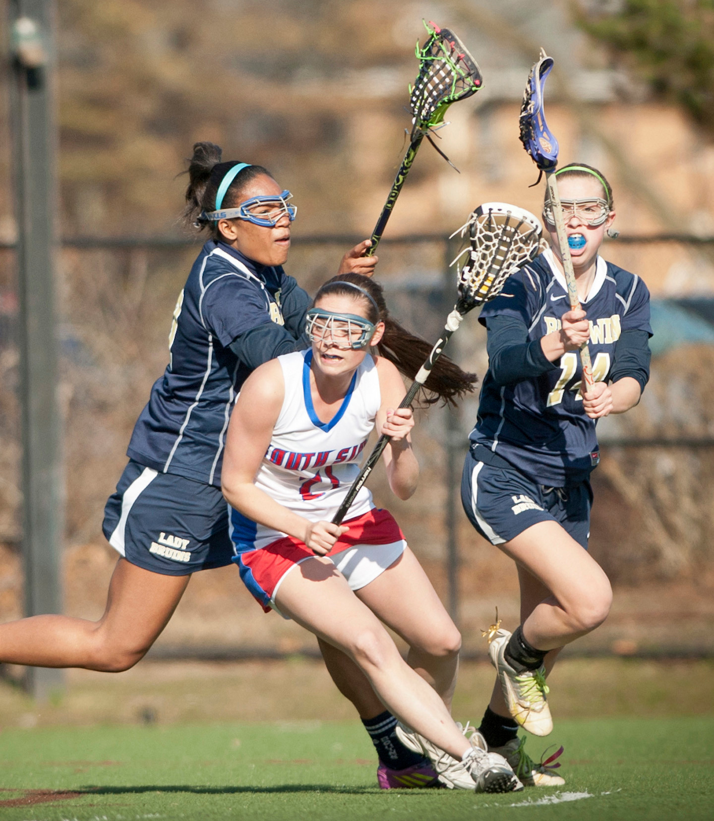 South Side's Michaela Lynch, center, avoids Baldwin's Kelsey Cohen, right, and Olivia Dominique during a 15-5 victory on April 3.