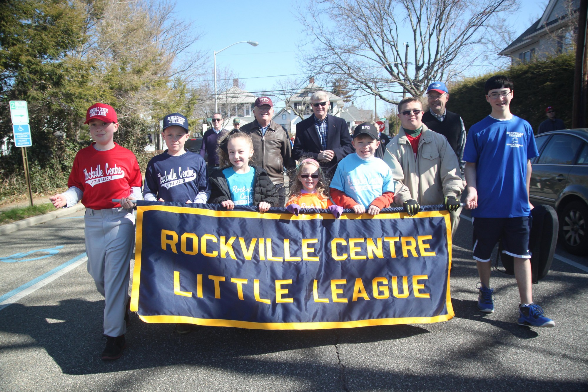 The Rockville Centre Little League kicked off its 2013 season last Sunday with its annual parade and food drive. The players collected more than 2,000 pounds of food this year. Holding the banner during the parade were, from left, Brian St. Pierre, JT Travers, Taylor Baetens, Delia Ryan, Ryan Kennedy, Connor Barry, and Alex Klein.