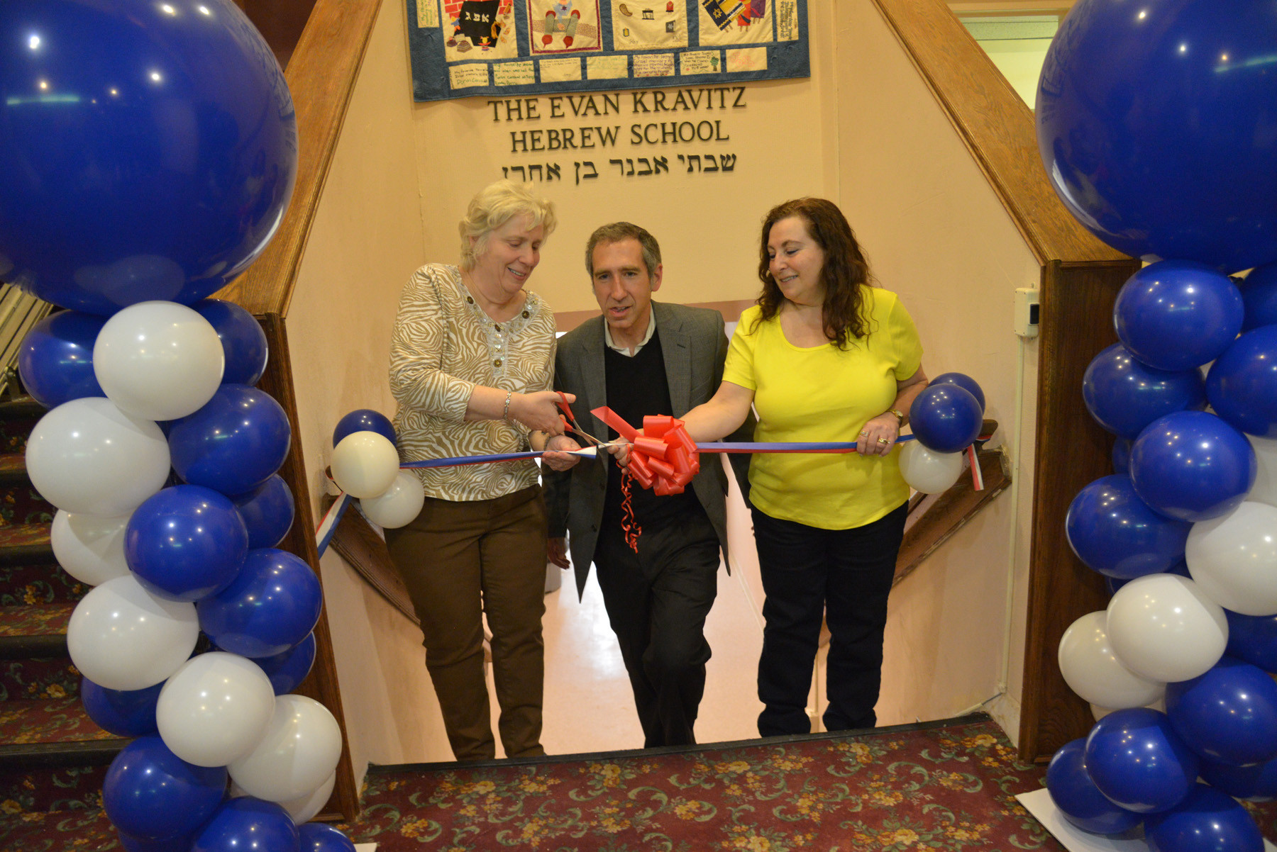 Temple president Barbara Rothstein, Rabbi Scott Hoffman and Executive Vice President Gail Kanner cut the ribbon on the rebuilt Hebrew school.
