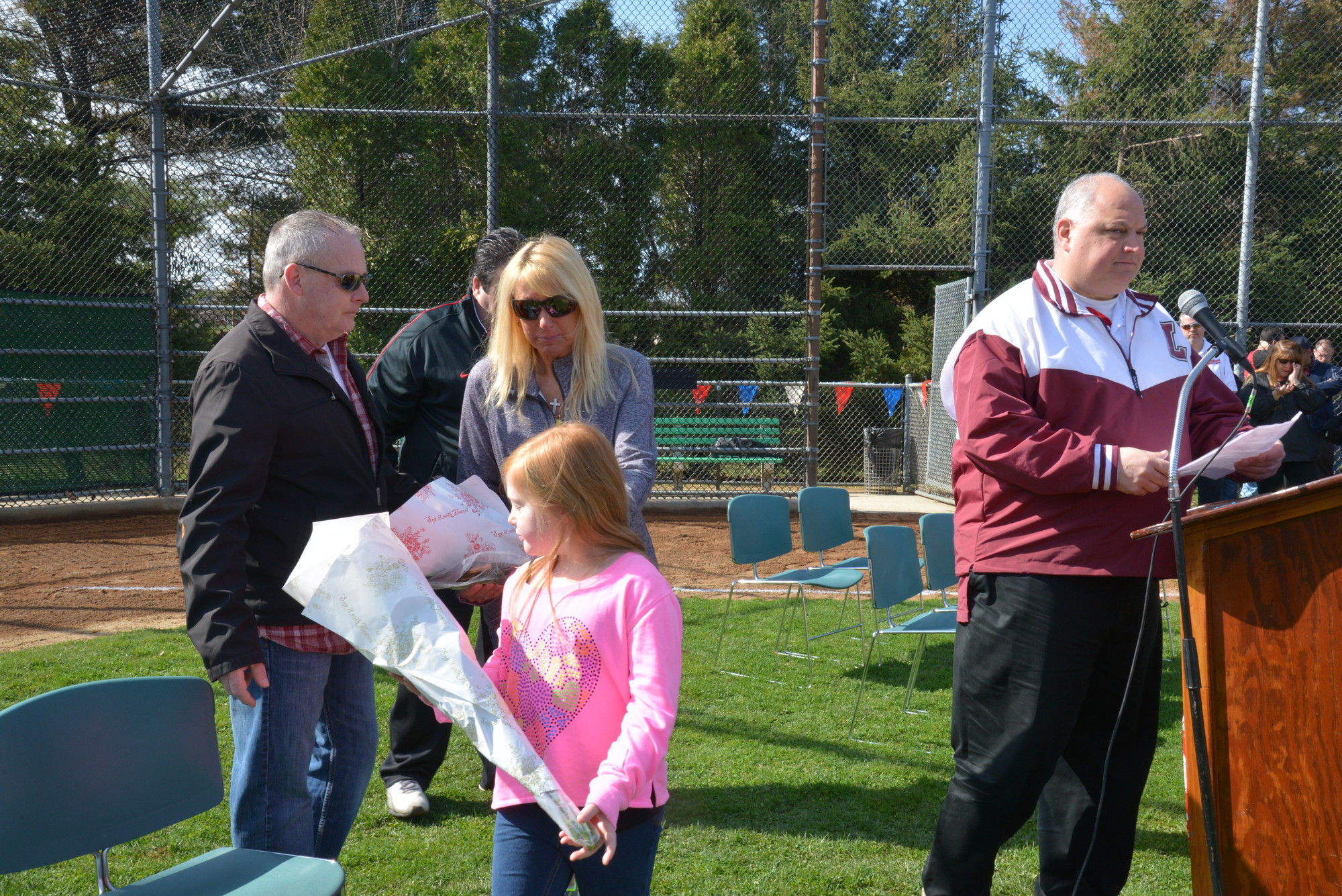 The family of Harlie Treanor, father Kevin, mother Joy Ambrosio and sister Maddie, with league president Joe Aloi during the Central Nassau Little League Parade, which was dedicated to Harlie.