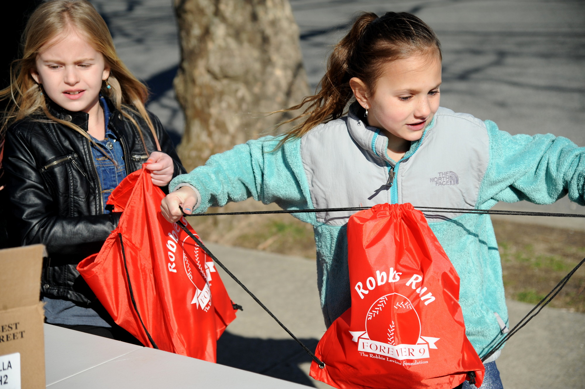 Ally Greenberg, 7, and Eden Rothstein, 7, from left, helped pack bags in preparation for the upcoming Robbie's Run on Sunday, April 28.