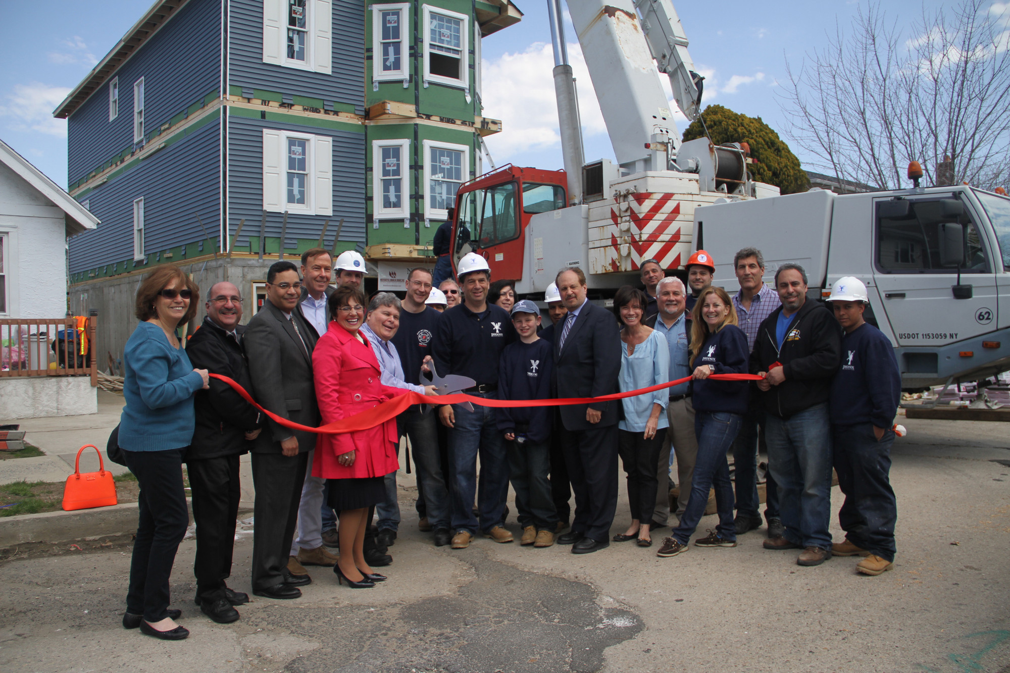 Homeowner Michael Seeman, eighth from left, cut the ribbon to mark the installation of his new home with the Chamber of Commerce and workers.