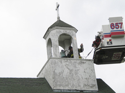 Capt. George Serviss, pictured in the tower at St. Mark's, and firefighter Pat Ryan, in the bucket, helped repair the bell's rope.