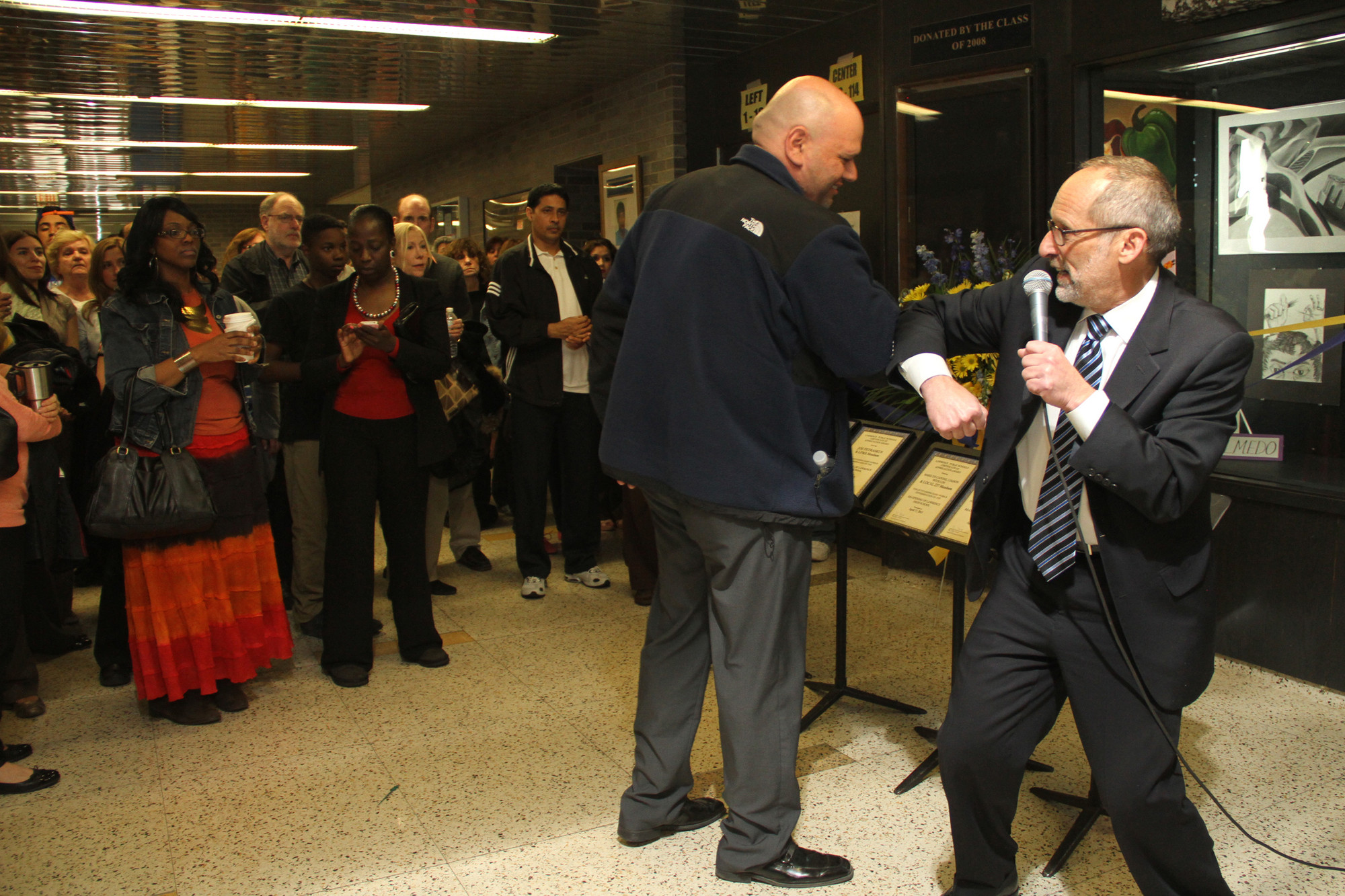 Gary Schall greets Facilities Director Chris Milano with an elbow bump at the ribbon-cutting.