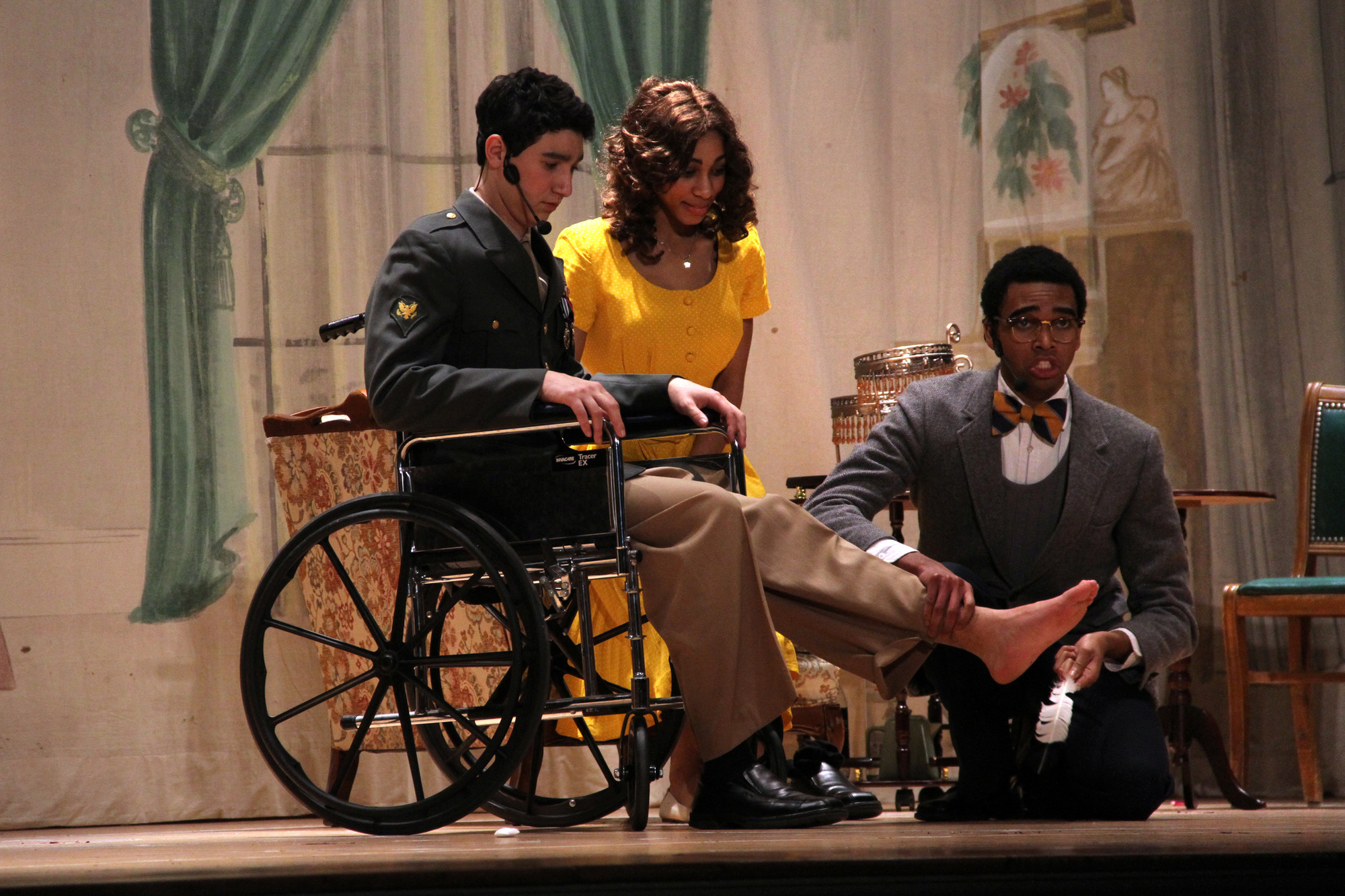 In one of the play's scenes, Brandon Funderburke as Lawrence Jameson pretended to be doctor and checked the foot of Freddy Benson, played by Joshua Torres. Amber Garrick as Christina Colgate waited for the diagnosis.