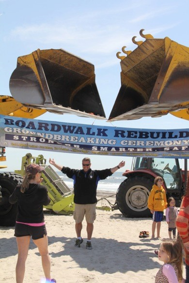 Ed Ryan stands under the bulldozers that will help build the new boardwalk