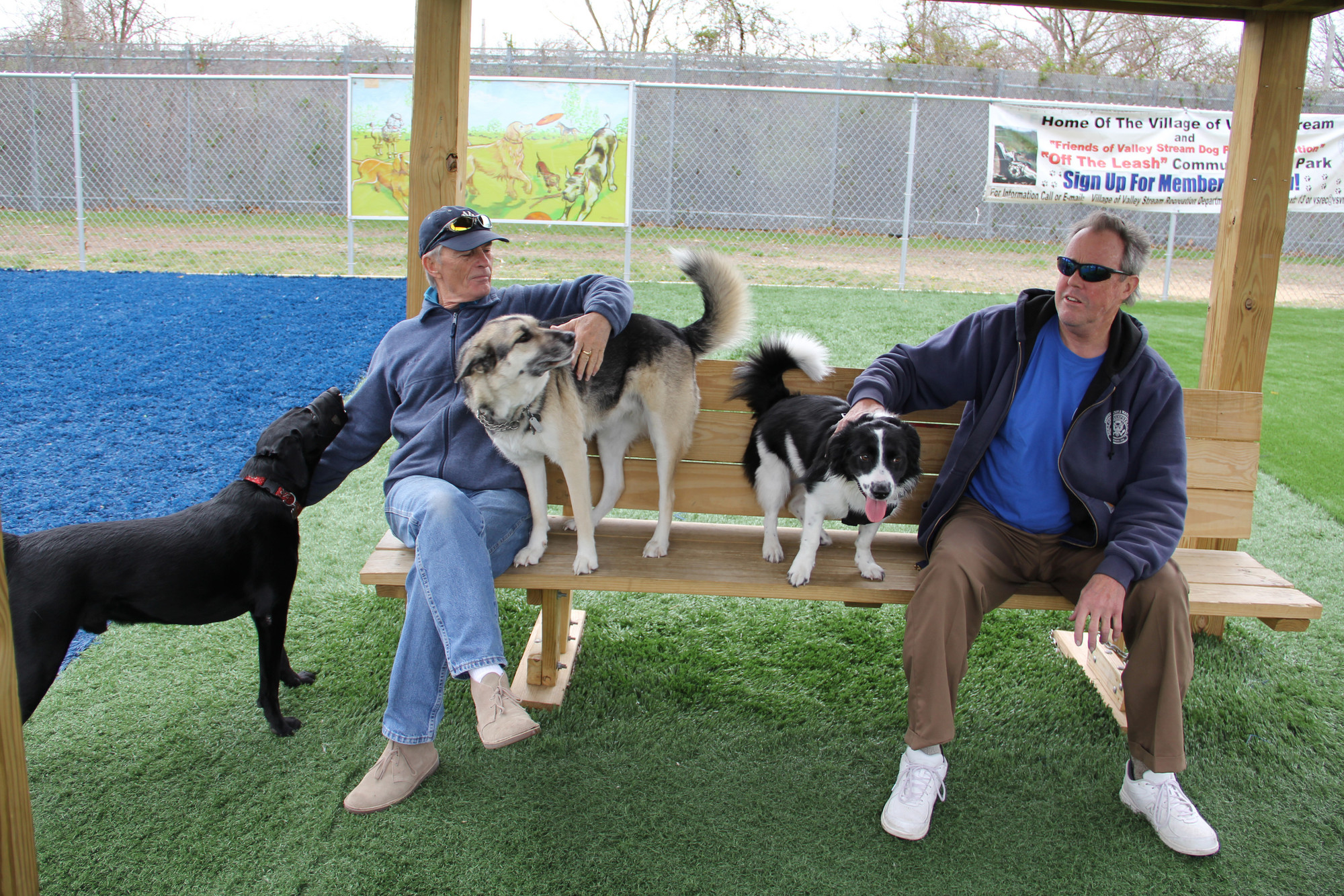 John McSwiggan left with Black Lab Beau and Husky Shepard Terrier Lady sits with David Walsh and Lola a Border Collie Mix at the Valley Stream Dog Park.