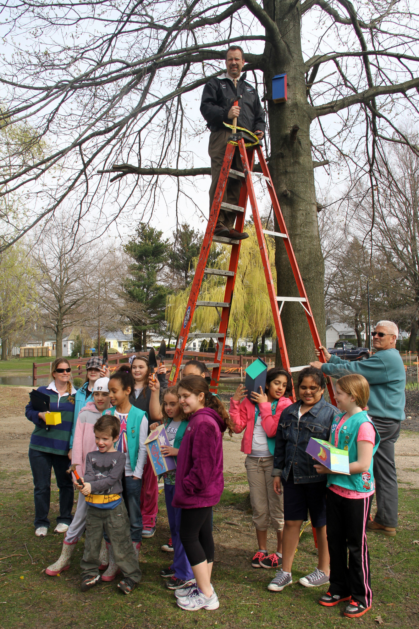 Mayor Ed Fare hung bat houses that Girl Scout Troop 2029 made for the park.