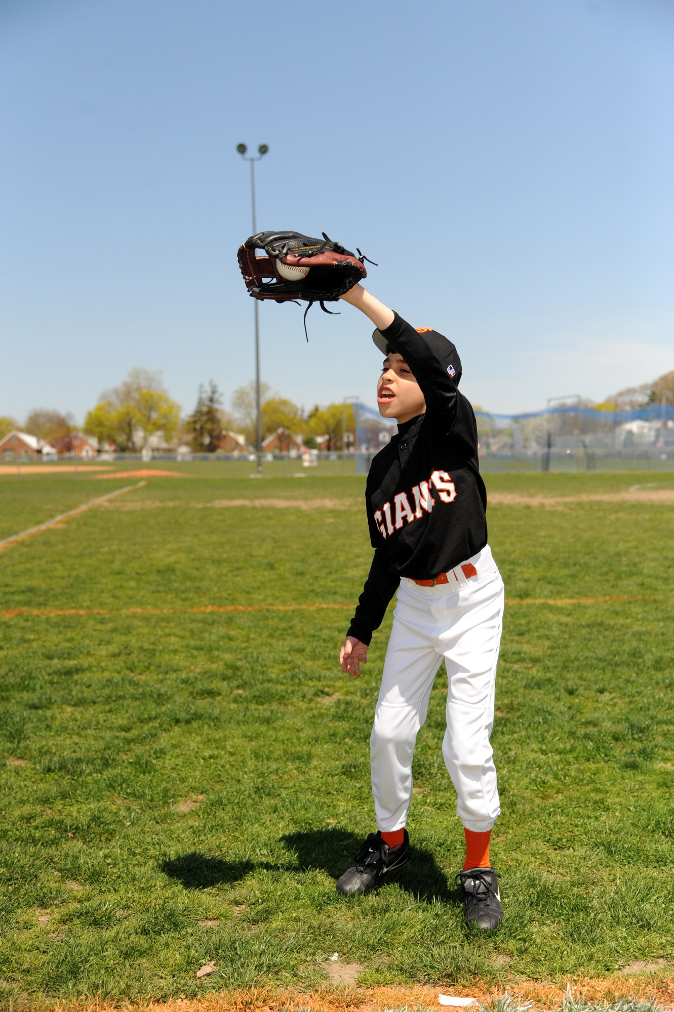 Adrian Quezada, 8, played catch to warm up for his first game of the season.