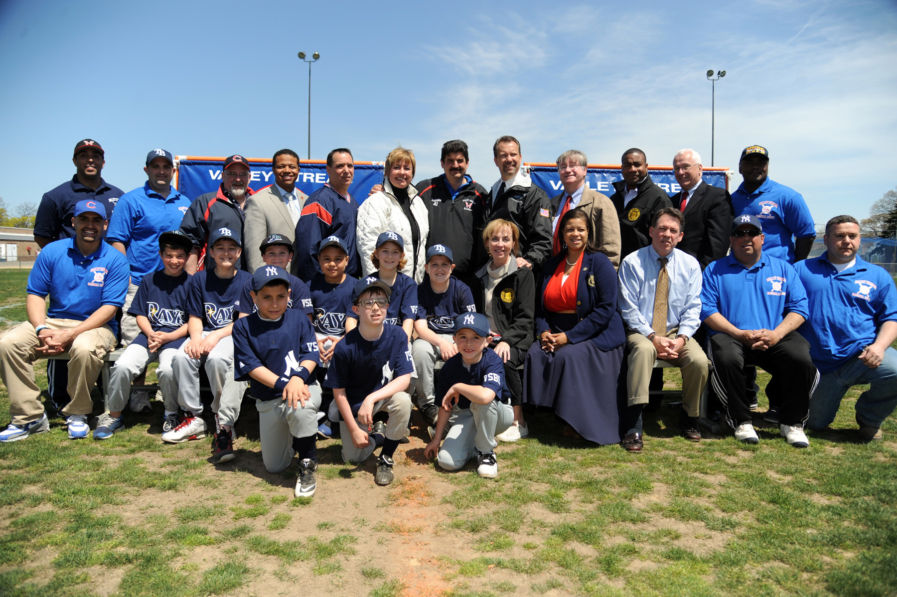 Members of the Rays and Yankees, Valley Stream Baseball League coaches and officials and politicians celebrated the league's 71st Opening Day on Saturday afternoon at Firemen's Field. Standing third from left were Valley Stream Deputy Village Clerk Rich DeAngelis, Leg. Carrie Solages, Trustee John Turfarelli, Town of Hempstead Supervisor Kate Murray, Valley Stream Baseball League President Bob Inzerillo, Mayor Ed Fare, Justice Robert Bogle, Deputy Mayor Dermond Thomas and Town of Hempstead Councilman James Darcy. Sitting from center, Trustee Virginia Clavin-Higgins, Assemblywoman Michaelle Solages and Leg. Fran Becker.