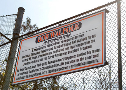 A sign recognizing Walpole hangs above the Carey dugout.